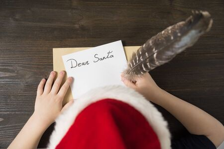 Child writes letter to Santa In santa's hat. Wooden background. Christmas concept