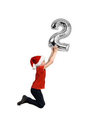 Silver inflatable number 2 in the hands of a jumping boy in a red hat. White background