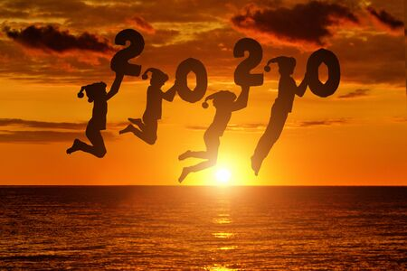 Silhouette of number 2020 in the hands of jumping children. Sunset sky and sea on background. New years concept