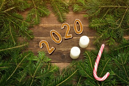 Number 2020 from gingerbread cookies. Wooden background. Spruce branches, candy and candles. Christmas concept.