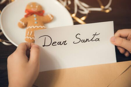 Childrens hands put a letter for Santa in an envelope. Wooden background. Close-up Stok Fotoğraf