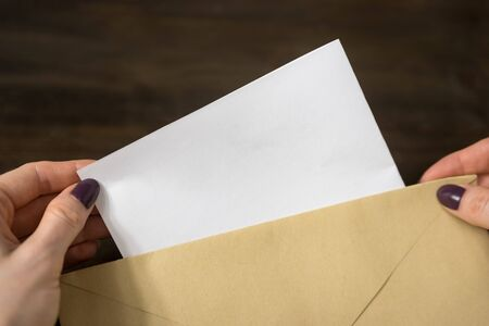 Female hands put a letter in an envelope. Wooden background. Close-up