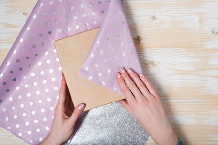 Female hands pack a gift in a shiny violet polka-dot paper. Top view