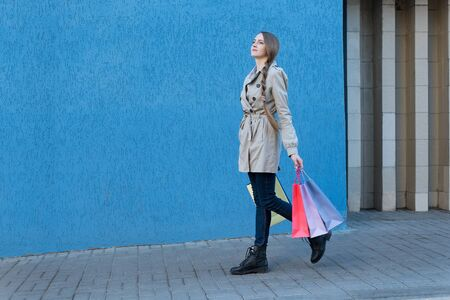 Pretty young woman with colorful bags walking on the street. Blue wall on background