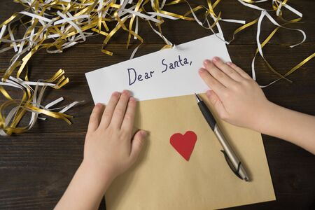 Children hands and the letter to Santa in envelope. Tinsel, wooden background. Stok Fotoğraf