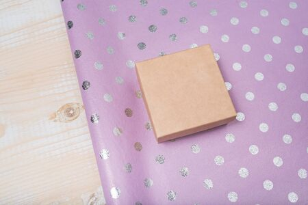 Small cardboard box and lilac polka dot wrapping paper. Wooden table. Preparation for the holiday