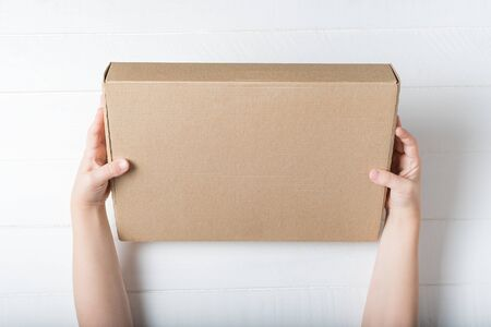 Rectangular cardboard box in childrens hands. Top view, white background Stok Fotoğraf