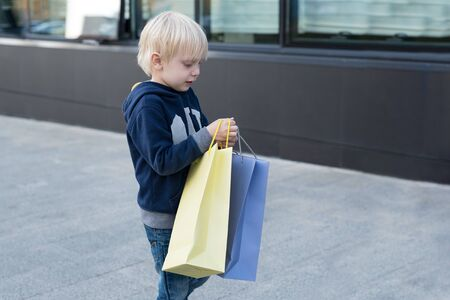 Little blond boy with shopping bags. Family shopping