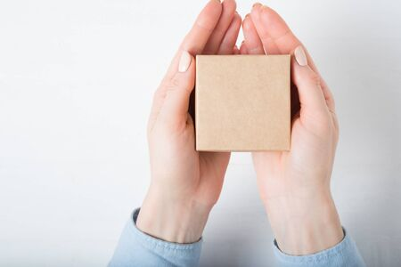 Small square cardboard box in female hands. Top view, white background Stok Fotoğraf