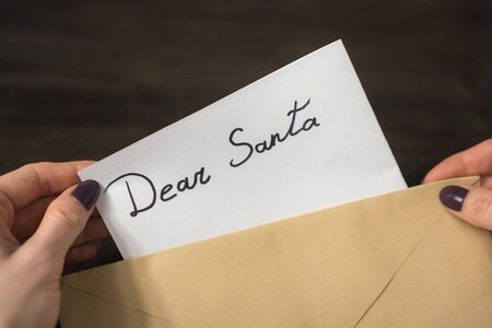 Female hands put a letter for Santa in an envelope. Wooden background. Close-up Stok Fotoğraf