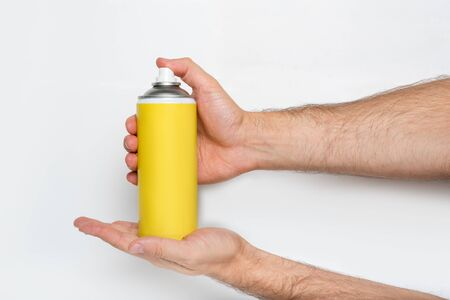 Yellow spray can for spraying in a male hands. No inscriptions. White background