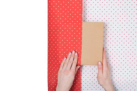 Female hands pack a gift in white-red polka-dot paper. White copy space. Top view