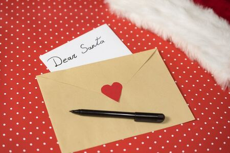 Letter for Santa in an envelope, pen. Santa hat. Red polka dot background