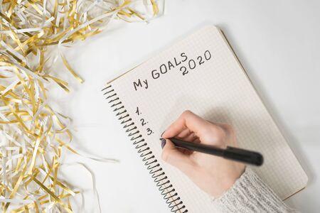 Mains féminines écrivant Mes objectifs 2020 dans un cahier. Tinsel, concept du nouvel an