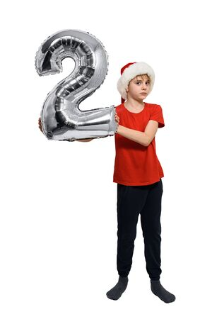 Number 2 of a silver balloon in the hands of a blond boy in a red Santa hat. White background. Stok Fotoğraf