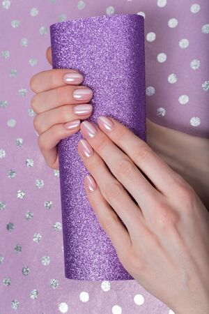 Fashionable female manicure. Shiny purple background. Polka dot background