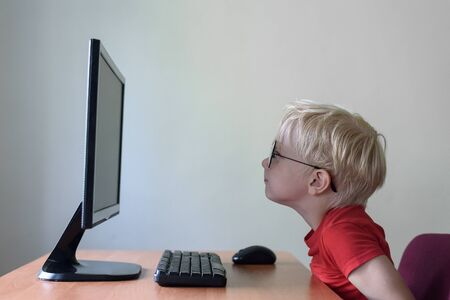 Blond boy with glasses sits his nose buried in a monitor. Internet and preschooler