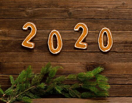 Number 2020 made from gingerbread cookies on a wooden background. Spruce twigs. New Year concept