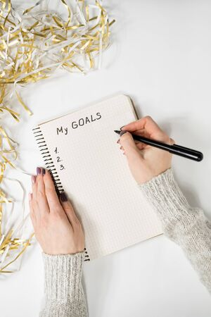 Female hands writing My Goals in a notebook. Tinsel, New Years concept