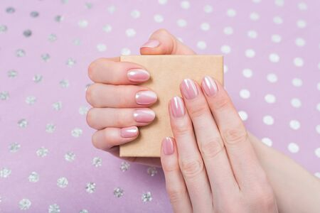 Small cardboard box in female hands. Delicate pink manicure. Lilac polka dot background Stok Fotoğraf