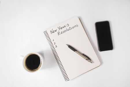 Phrase New Years Resolutions in the notebook and pen. Cup of coffee and smart phone on table