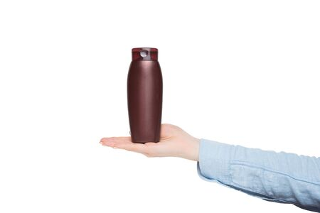 Brown bottle for cosmetic in a female hand. Mockup. Isolate