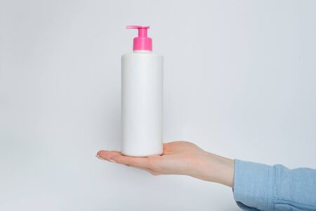 White cosmetic plastic bottle with pump in female hand. White background Stock Photo