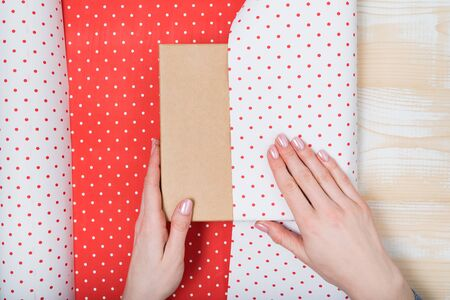 Female hands pack a gift in white-red polka-dot paper. Top view