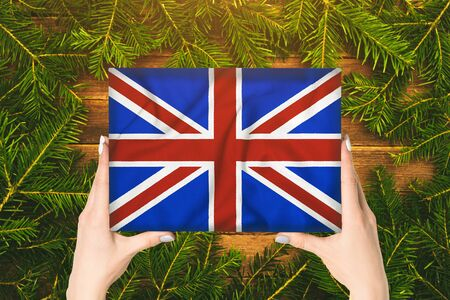 Box with Great Britain flag in female hands. Fir branches on the background Stok Fotoğraf