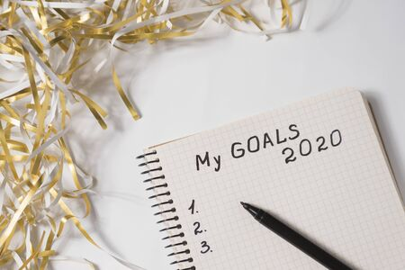 Phrase My Goals 2020 in a notebook, pen. Tinsel on white background. Close up