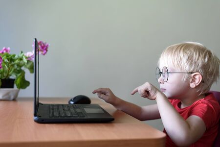 Funny blond boy in glasses sits at a laptop. Internet and preschooler