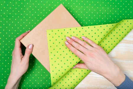 Female hands pack a gift in a green polka-dot paper. Top view