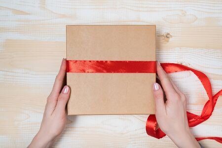 Female hands tie a red ribbon on a gift box. Wooden table. Top view
