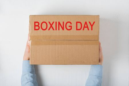 Boxing day. Large cardboard in female hands. White background