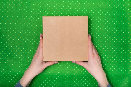 Square cardboard box in female hands. Top view, green polka dot background