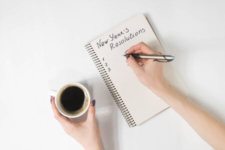 Phrase New Years resolutions in the notebook. Female hand with pen and cup of coffee