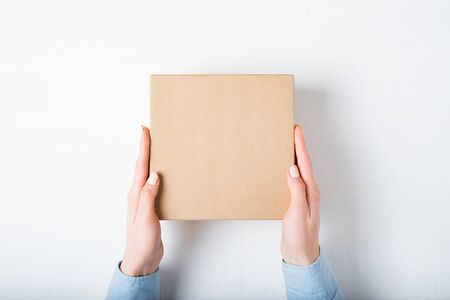 Square cardboard box in female hands. Top view, white background Stok Fotoğraf