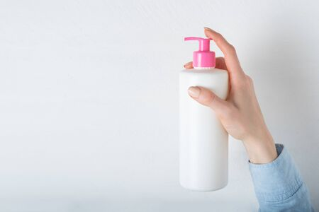 White cosmetic plastic bottle with pump in female hand. White background Stok Fotoğraf