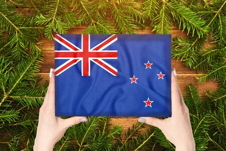 Box with New Zeland flag in female hands. Fir branches on the background Archivio Fotografico