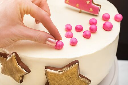 Female hand adjusts decorations on a festive cake. Close up.