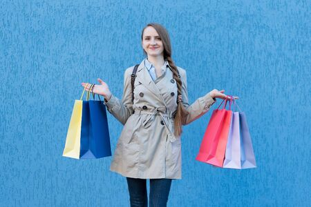 Happy young woman shopaholic with colorful bags. Blue street wall on background