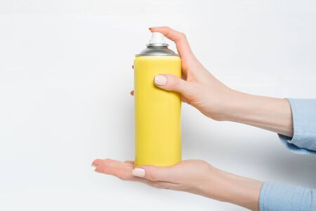 Yellow spray can for spraying in a female hands. No inscriptions. White background Stockfoto