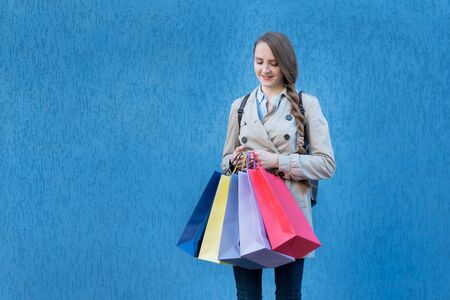 Young woman shopaholic with colorful bags. Blue street wall on background