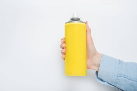 Yellow spray can for spraying in a female hand. No inscriptions. White background Stok Fotoğraf