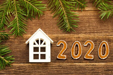 Small white house and number 2020 from gingerbread cookies. Fir branches, wooden background.