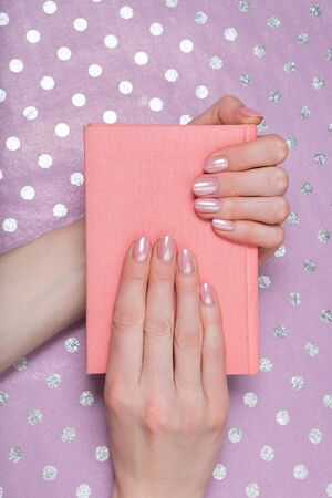 Pink notebook in female hands. Shiny paper on background Stok Fotoğraf