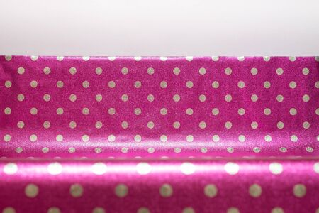 Raspberry shiny wrapping paper with polka dots with a fold. Foil for the design of gift wrapping, wallpaper. Stylish shiny texture Stok Fotoğraf
