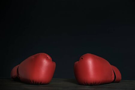 Pair of red boxing gloves on a black background. Copy space