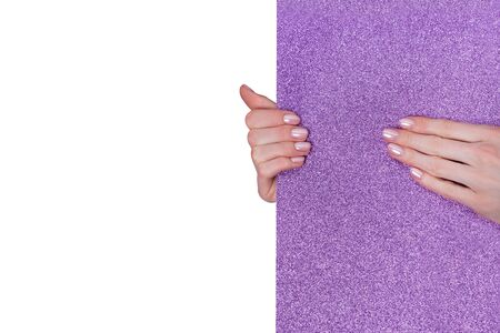 Fashionable female manicure. Shiny purple background. White copy space