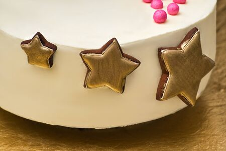 Birthday cake with golden gingerbread stars. Close up.
